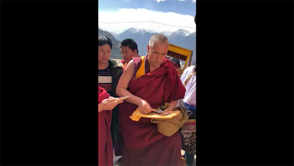 Ven Lobsang Jigme of Tsem Monastery in Yara, Tibet is passing out pictures of Tsem Rinpoche to the locals.